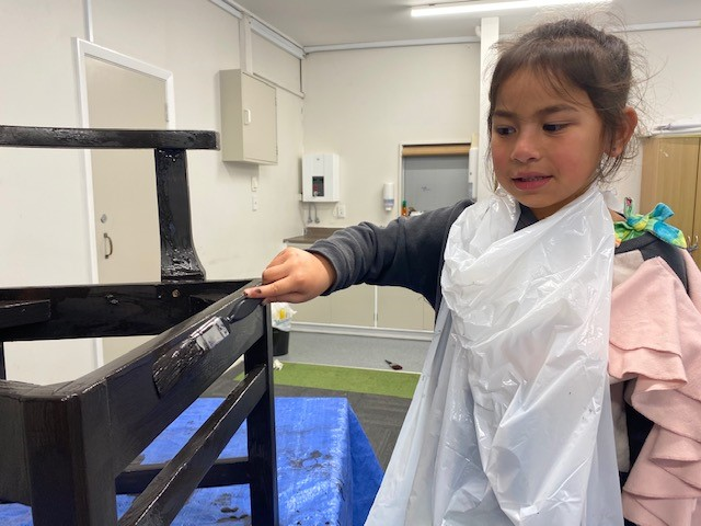 A tamariki paints a chair as part of the zero-waste project