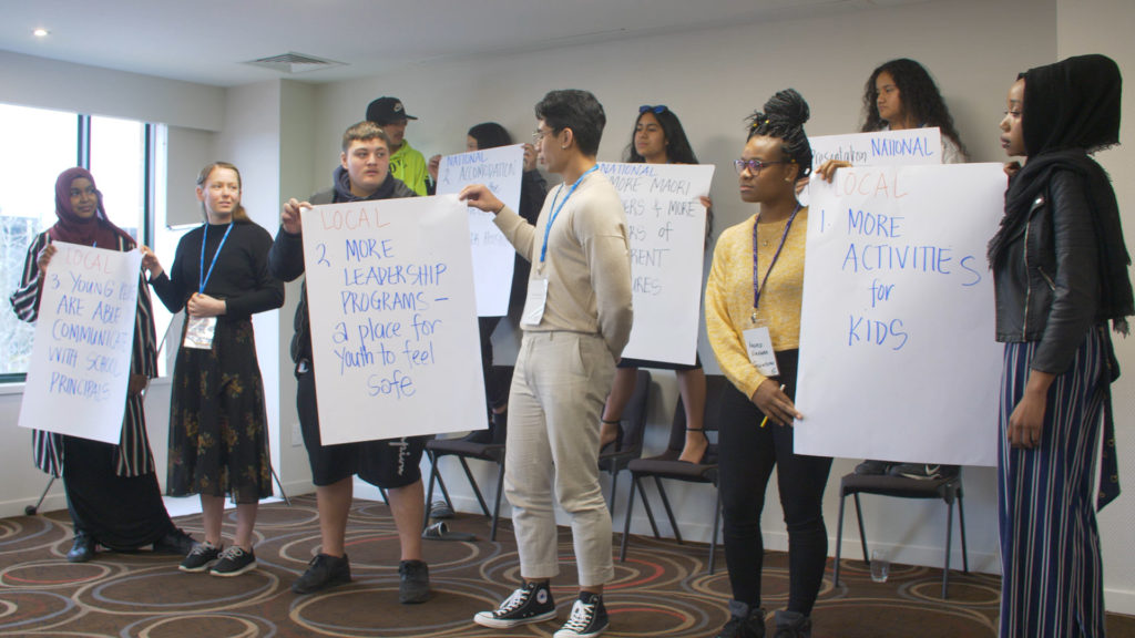 A group of 11 young people prepare to report back to the main group at the PALMs 2019 Symposium